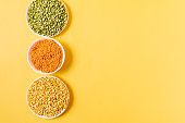 Top view of assortment of peas, lentils, beans and legumes over yellow background.