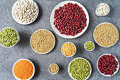 View directly above of assortment of peas, lentils, beans and legumes over gray background.