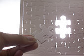 Hands holding one last piece of jigsaw puzzle in white back light background with unfinished white jigsaw puzzle pieces