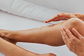 Woman applying cream on legs on bed