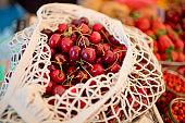 Cherry in reusable bag on a farmers market, zero waste concept