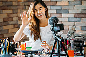 Smiling Asian woman waving hand on camera at table with cosmetics