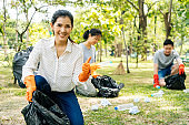 Young Asian woman smiling, giving thumbs up with friends wearing orange gloves and collecting trash in garbage bag in the park