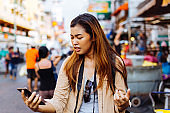 Traveling woman with broken phone on street
