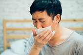 Young Asian man coughing and suffering in medical mask inside home bedroom - illness and fever concept.