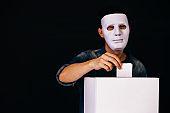 Masked criminal holding ballot paper casting fake vote at a polling station for election vote in black background.