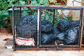 Bags with litter inside cage in nature