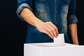 Front view of person holding ballot paper casting vote at a polling station for election vote in black background