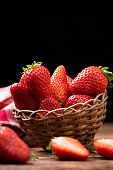 Strawberries in a basket on old wooden table