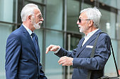 Two senior businessmen meeting and discussing in front of an office building.