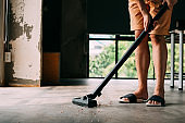 Human legs wearing sandals using vacuum cleaner inside the house