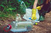 Volunteer collects garbage - plastic bottles in spring or summer outdoors
