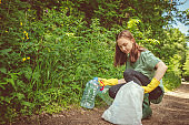 Volunteer girl collects garbage - plastic bottles in spring or summer outdoors