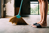 Human legs wearing slippters using sweeping broom inside the house
