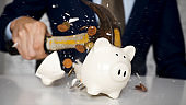 Close-up of businessman using a hammer to smash plenty of coins inside piggybank into pieces as he needs emergency money - using money in financial crisis concept.