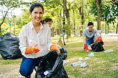 Young Asian woman and group of volunteers wearing orange gloves and collecting garbage in trash bin bag in the park