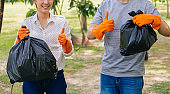 Young Asian male and female couple volunteers with gloves giving thumbs up while collecting garbage waste into trash bag in green park
