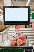 Apples in reusable bag on scales in a supermarket, zero waste concept