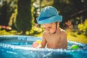 Cute little boy having fun in swimming pool at back yard in summer