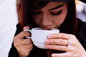 Close up of smiling young woman drinking coffee outdoor