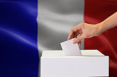 Close-up of human hand casting and inserting a vote and choosing and making a decision what he wants in polling box with France flag blended in background.