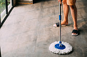 Man cleaning up living room using mopping tool