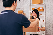 Happy Asian adult business female in the office receiving a parcel from male deliverman