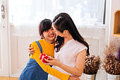 Smiling happy Asian teenage daughter and Asian middle-aged mother hugging together in indoor living room at home