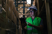 Young Asian male warehouse worker using a digital tablet inside warehouse