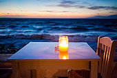 romantic table with burning candle by the sea at night