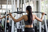 Woman pump back muscles exercise in gym