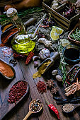 Olive oil bottle with a variety of allspice ingredients and condiments for food seasoning on table in old fashioned kitchen