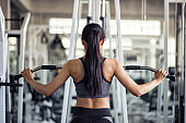 woman exercise by pumping back in gym