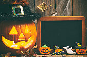 Halloween composition with chalkboard and gingerbread cookies on rustic wooden background