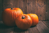 Thanksgiving concept with colorful pumpkins and fall leaves on rustic wooden background