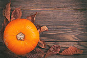 Autumn leaves and pumpkin on rustic wooden table