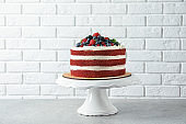 Stand with delicious homemade red velvet cake near brick wall