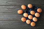 Raw chicken eggs in ceramic holder on wooden background, top view. Space for text