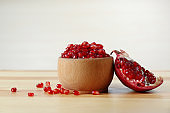 Bowl with pomegranate seeds and fresh fruit on table against light background