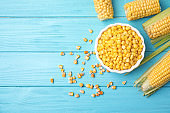 Flat lay composition with corn kernels on blue wooden background. Space for text