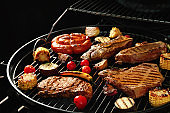 Fresh grilled meat steaks and vegetables on barbecue grate