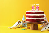 Delicious homemade red velvet cake with candles on yellow background. Space for text