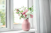 Vase with beautiful flowers on window sill