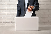 Man putting his vote into ballot box on table against brick wall, closeup