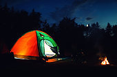 Glowing camping tent near bonfire in wilderness at night