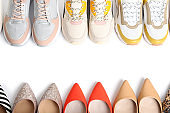 Frame of different shoes on white background, top view with space for text