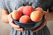 Woman holding bowl with delicious ripe peaches, closeup