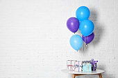 Bunch of bright balloons and gifts on table against white brick wall, space for text