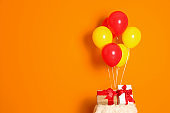 Bunch of bright balloons and gifts on table against color wall, space for text