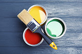 Flat lay composition with paint cans and brush on wooden background